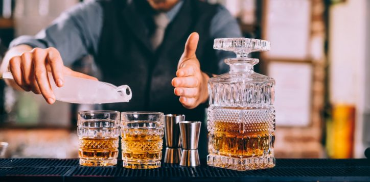 stock-photo-close-up-of-barman-hands-adding-ice-and-whiskey-to-modern-urban-cocktails-sky-bar-serving-elegant-764280106-2